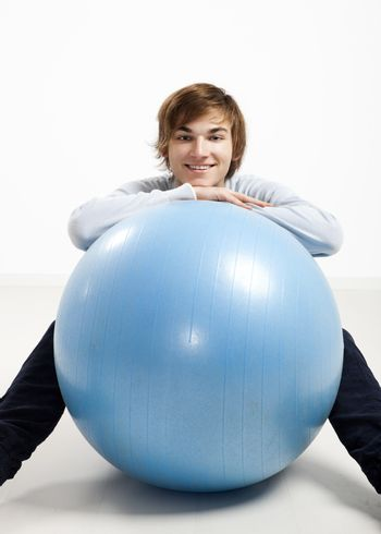 Young man over a pilates ball