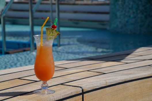 cool refreshing orange coctail at swimming pool on vacation