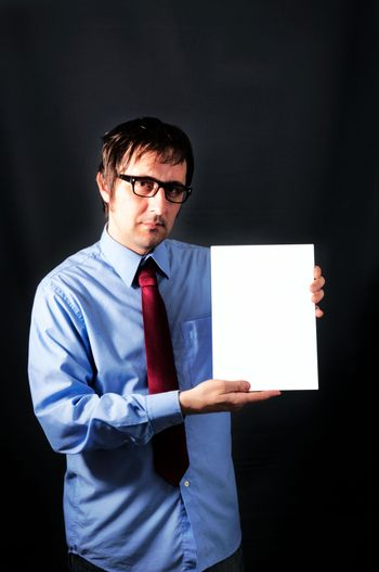 Businessman holding blank paper in low key technique light