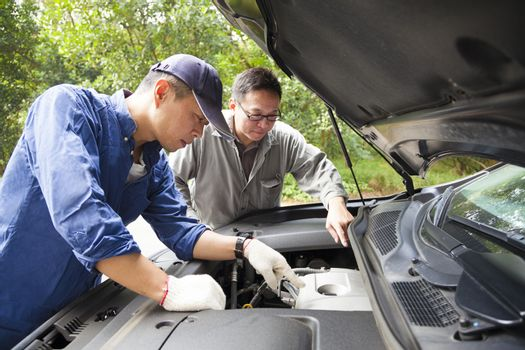 two Mechanics  fixing the car on the road
