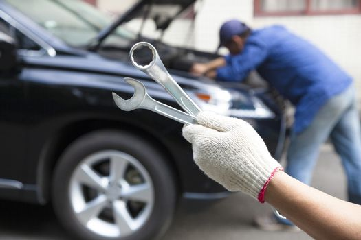 hand holding tools and car service concept