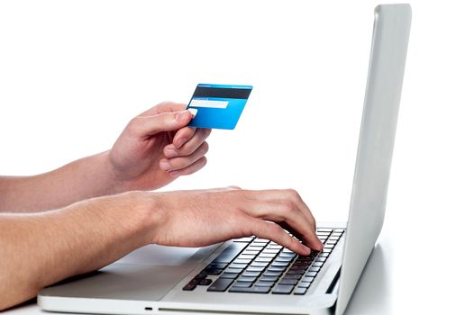 Mans hand holding debit card and using laptop