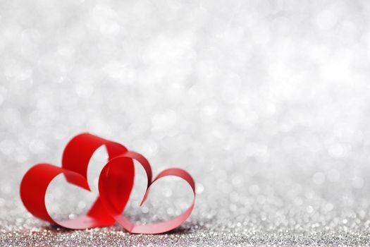 Red ribbon hearts on shiny glitter background