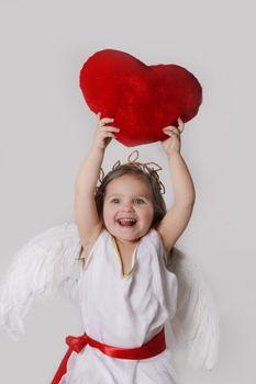 Joyful cupid girl holds plush heart over head isolated onmwhite