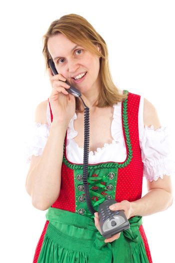 Woman in red dirndl dialing a friend