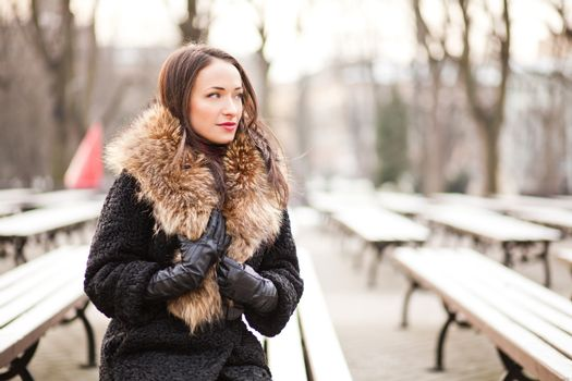 Young professional lady in the park is enjoying winter
