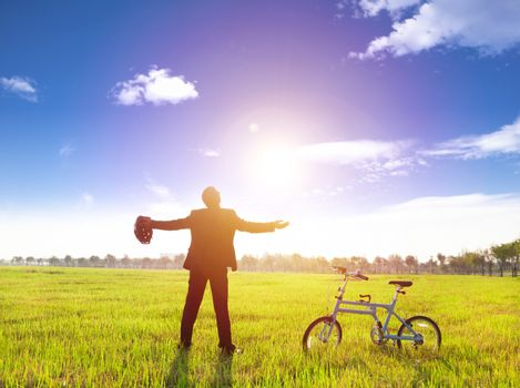 businessman relaxing in green land and sun with bicycle