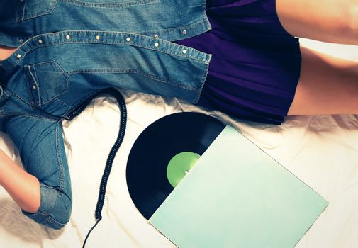 woman on bed with a vinyl record
