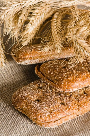 Rye bread and wheat on cloth sack, close-up
