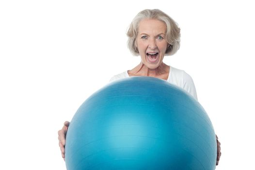 Aged woman posing with exercise ball