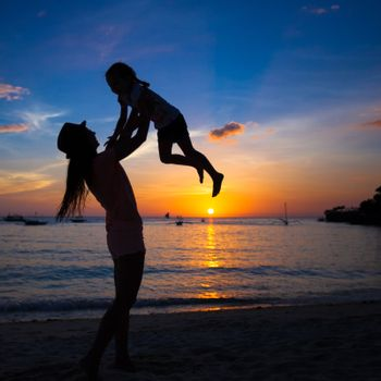 Silhouette of mother and little daughter playing on the beach of Boracay, Philippines