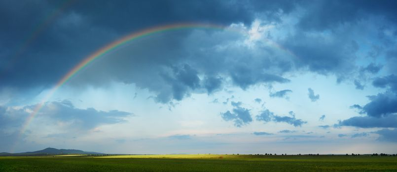 Rainbow arch over green spring field of South Bulgaria