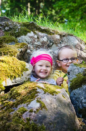 Young children, the boy with the girl hid among the rocks