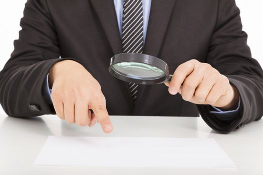 Businessman pointing through a magnifying glass to documents