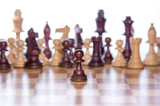 Beautiful chessboard with chessfigures in the back and a focused pawn in the front