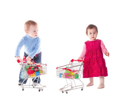 Boy and girl play with shopping trolley and toys, isolated on white