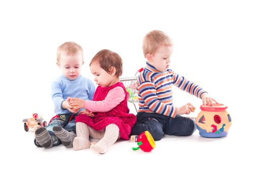 Three children play with toys isolated on white