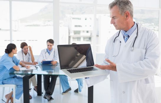 Doctor holding laptop with group around table in background at hospital
