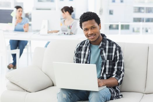 Young man using laptop with colleagues in background at a creative bright office