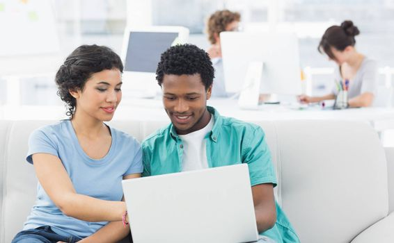 Casual couple using laptop with colleagues in background at a creative bright office