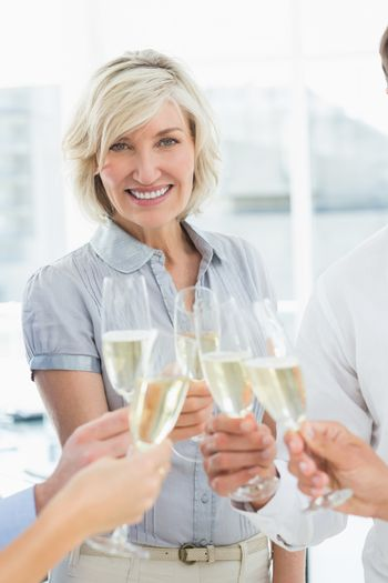 Portrait of a happy businesswoman toasting with champagne in the office