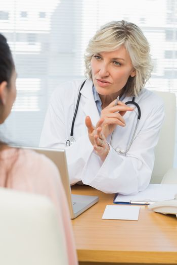 Female doctor listening to patient with concentration