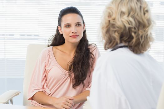 Female patient listening to doctor with concentration in medical office