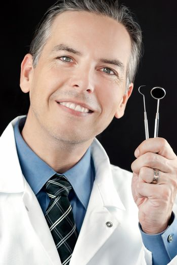 Close-up of a smiling dentist holding his tools