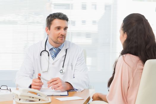 Doctor listening to patient with concentration at desk
