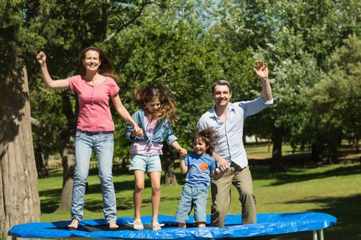 Happy family jumping high on trampoline in park