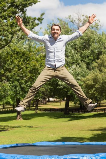Happy man jumping high on trampoline in park
