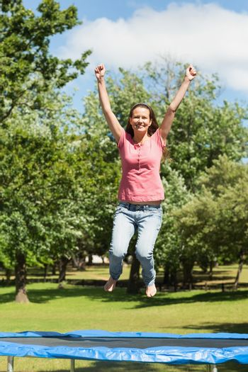 Happy woman jumping high on trampoline in park