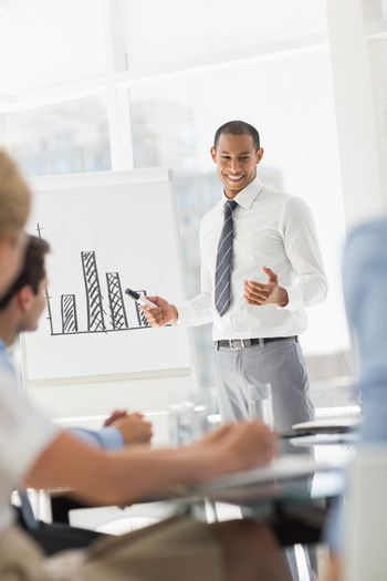 Smiling young businessman presenting bar chart to co workers