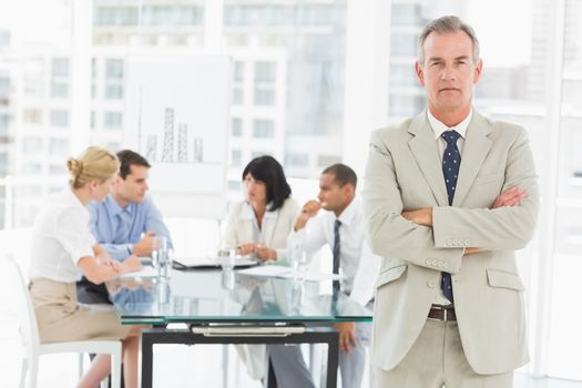 Serious businessman looking at camera while staff discuss behind him