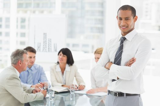 Young businessman looking at camera while staff discuss behind him