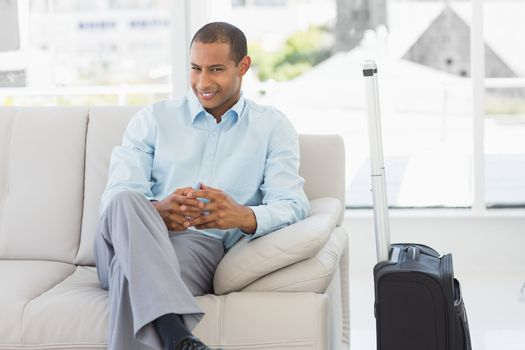 Happy businessman sitting on sofa waiting to depart on business trip