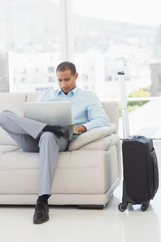 Businessman using laptop sitting on sofa waiting to depart on business trip