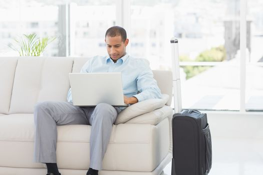 Businessman using laptop waiting to depart on business trip