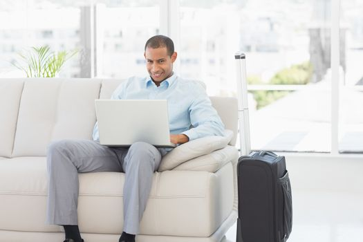 Happy businessman using laptop waiting to depart on business trip