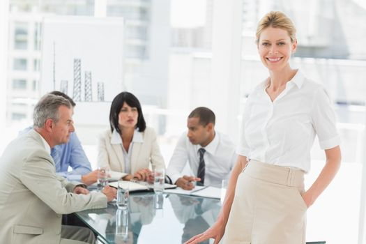 Happy businesswoman looking at camera while staff discuss behind her