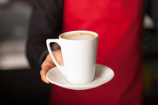 Hands of waiter serving a cup of cappucino
