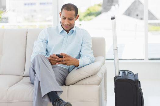 Man sitting on sofa sending a text waiting to depart on business trip