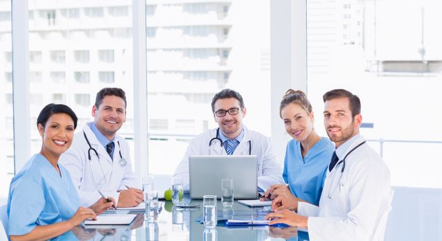 Portrait of a smiling medical team around desk in the office
