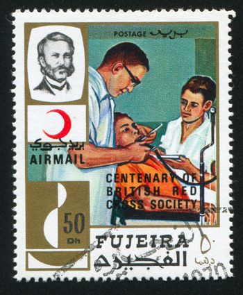 FUJEIRA - CIRCA 1976: stamp printed by Fujeira, shows Dentists and a Patient, circa 1976