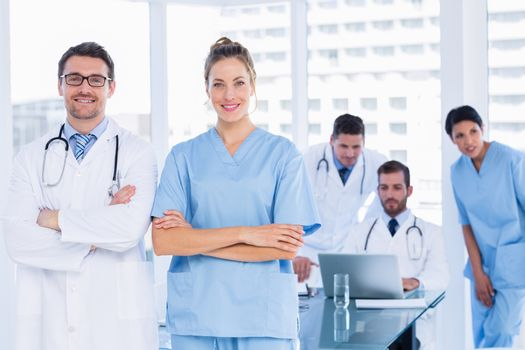 Portrait of doctors with colleagues using laptop behind in a medical office