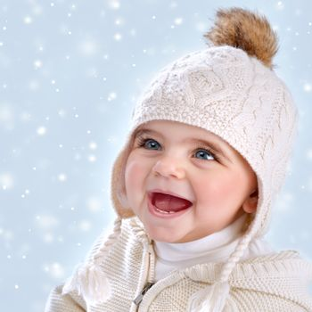 Closeup portrait of cute little baby girl wearing warm stylish hat isolated on blue snowy background, snow falling, winter season, happy child concept