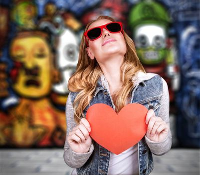 Graffiti urban lifestyle, funky culture, stylish teen girl wearing sunglasses and holding red paper heart, modern love concept