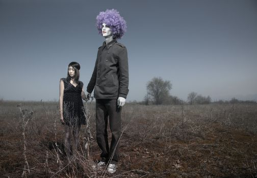 Bizarre couple outdoors. Little girl together with tall funnyman. Artistic colors added