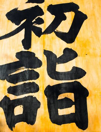 Japanese calligraphy, black letters on a yellow background