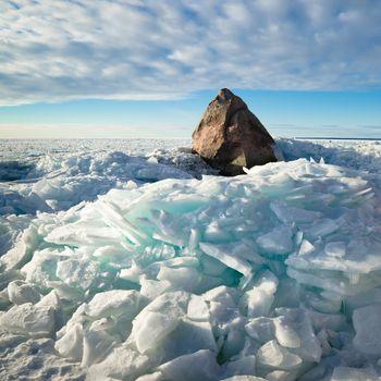 Big stone in the ice on the Baltic Sea coas